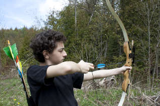 Teenaged boy doing archery outdoors