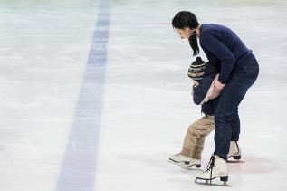 Mother helping child skate