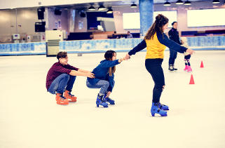 Teens skating pulling each other on ice