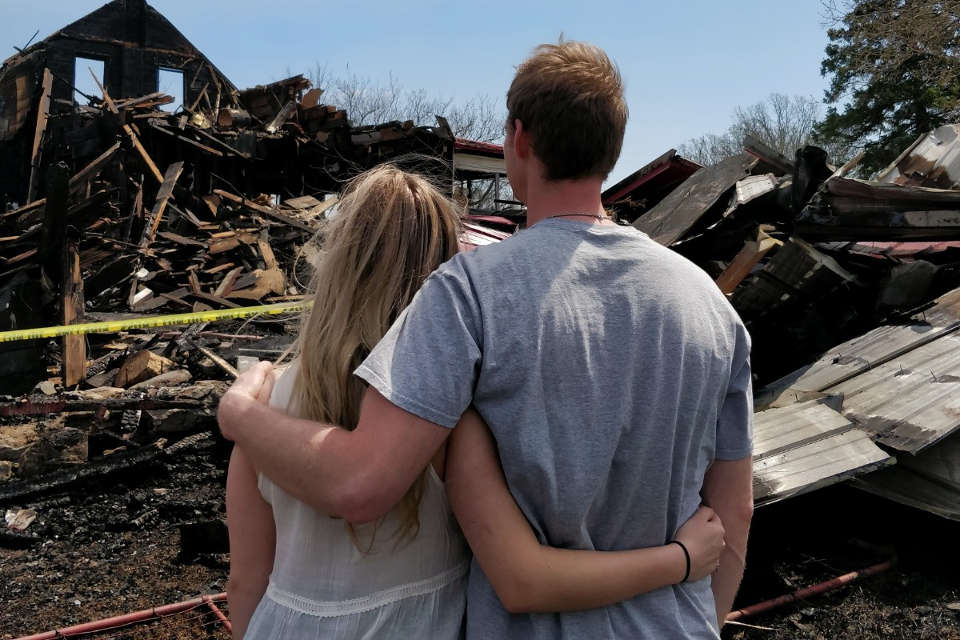 Couple facing burnt down house